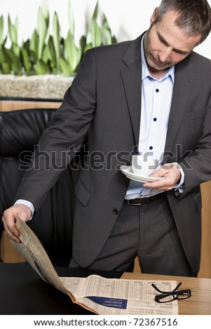 Smart businessman having a break, standing at office desk reading newspaper and drinking coffee. - stock photo
