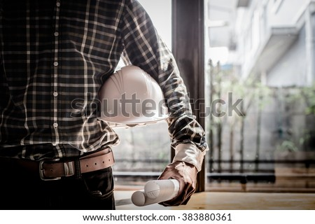 Smart Businessman holding construction helmet and blueprints in retro style. - stock photo