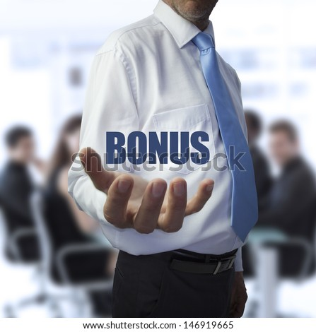 Smart businessman holding the word bonus in front of a business team - stock photo