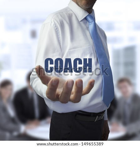 Smart businessman holding the word coach in front of a business team - stock photo