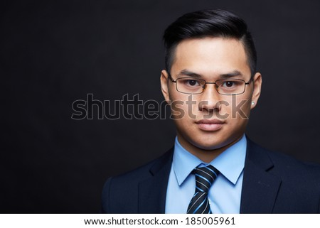 Smart businessman in formalwear and eyeglasses looking at camera - stock photo