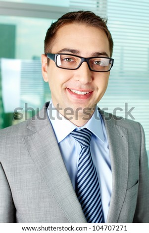 Smart businessman looking at camera and smiling - stock photo