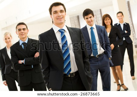 Smart businessman looking at camera at background of his friendly partners - stock photo