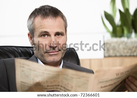 Smart businessman sitting in office chair reading newspaper and looking straight. - stock photo