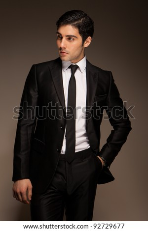 Smart Businessman standing and waiting in a three quarter pose dark studio portrait - stock photo