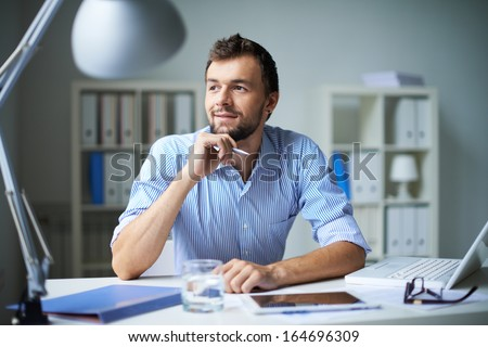 Smart businessman thinking about something in office - stock photo