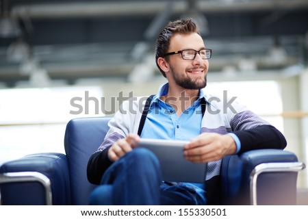 Smart businessman with touchpad thinking of new idea or strategy in office - stock photo