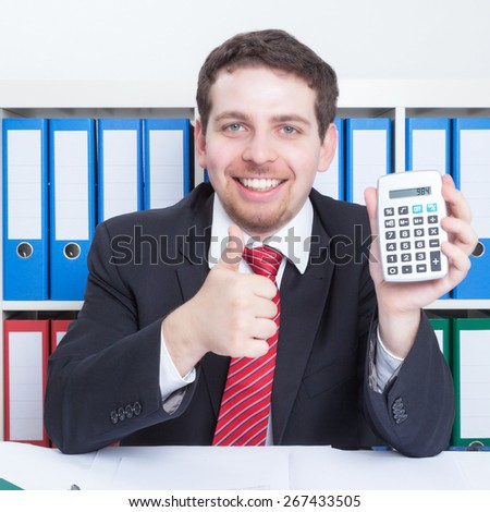 Smart businessmann in a black suit at office with calculator - stock photo