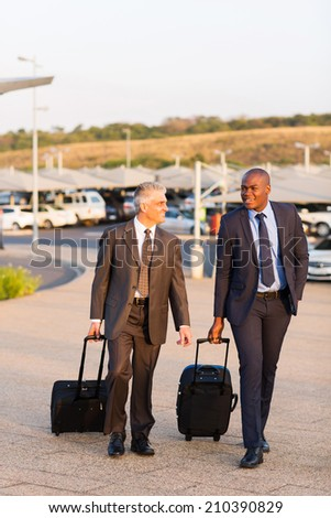 smart businessmen walking in airport parking lot - stock photo