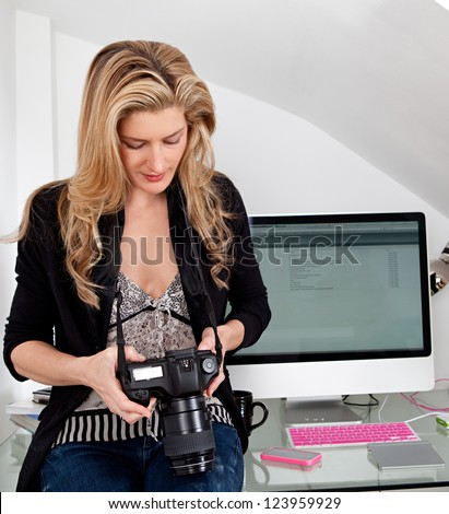 Smart businesswoman holding a professional digital photographic slr camera while sitting on her office desk.