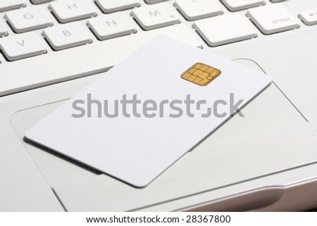 Smart card close-up on white laptop. Shallow DOF. Hard side light. - stock photo