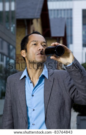 Smart casual business man drinking beer outdoors portrait in front of modern office building