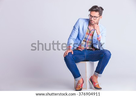 smart casual man seated on box, wearing glasses and jeans, posing while looking away in studio background - stock photo