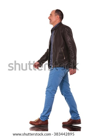 smart casual mature man in leather jacket walking in isolated studio background while looking away from the camera