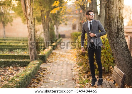 Smart casual outfit model in autumn park with leaves falling.