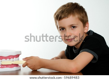 Smart Child with Fake Jaw at Dental Office - stock photo