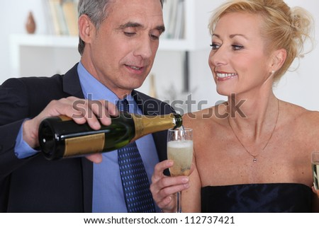 Smart couple drinking champagne - stock photo