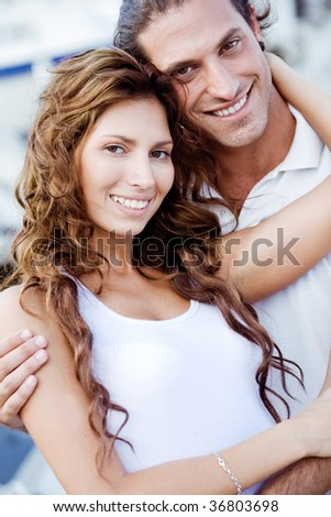 Smart couple posing at harbour holding hands tightly - stock photo
