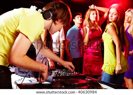 Smart deejay adjusting technics with dancing teens on background - stock photo