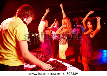 Smart deejay spinning turntables with dancing teens on background - stock photo