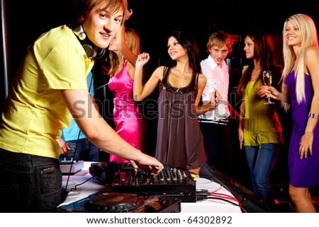 Smart deejay working at disco with dancing teens on background