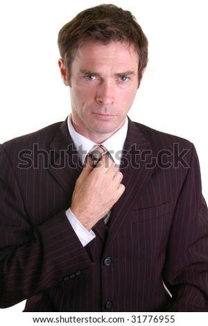 smart dressed business man adjsuting his tie - stock photo