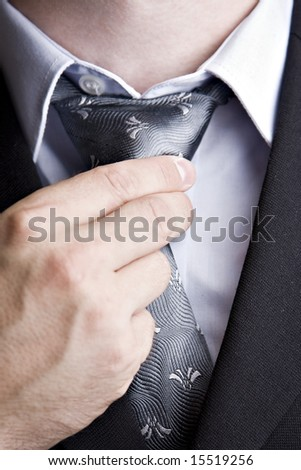smart dressed man adjusting his tie