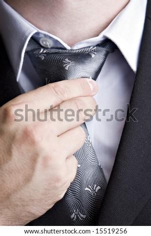 smart dressed man adjusting his tie - stock photo