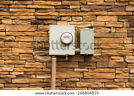 Smart Electric Utility Meter mounted on Natural Stone Wall. - stock photo