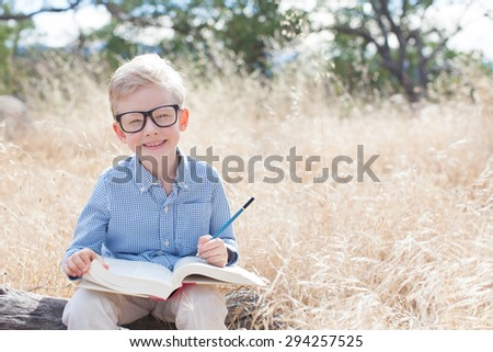 smart excited little boy in glasses studying with book and pencil ready for school, back to school concept - stock photo