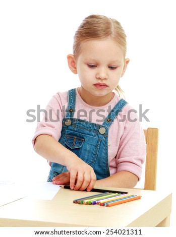 Smart girl draws pencils sitting at the table . Isolated on white.
