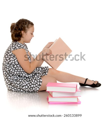 smart girl schoolgirl reading a book sitting on the floor - isolated on white. - stock photo