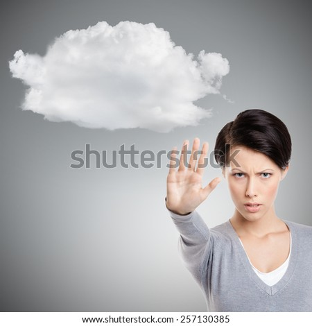 Smart girl shows stop gesture to cloud, isolated on  grey, close up - stock photo