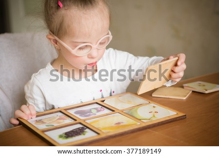 smart girl with Down syndrome collects puzzles - stock photo
