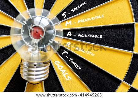 SMART GOALS and Big bulb target on bullseye with dartboard background symbol of big idea to success, Business finance success concept - stock photo