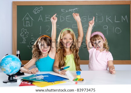 smart group of student kids at school classroom raising hand - stock photo