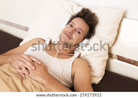 Smart guy in white undershirt lies in bed and listens to music