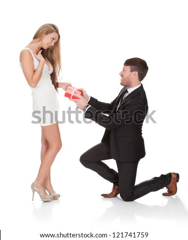 Smart guy kneeled on his knees then gives gift to wife. - stock photo