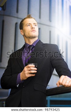 Smart Handsome Businessman Holding Drink In Hand While Staring Off Into The Future Of Dreams And Aspirations - stock photo
