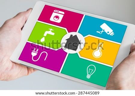 Smart home automation and mobile computing concept. Hands holding modern white and silver tablet with home automation dashboard screen.  - stock photo