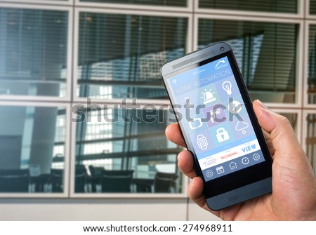 smart house, home automation, device with app icons. Man uses his smartphone with smarthome security app to monitor and control his office - stock photo