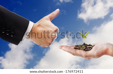 Smart Investment concept- Hand like and hand with seed and coins over cloud background - stock photo