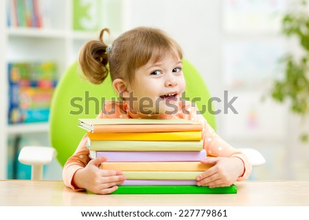 Smart kid girl preschooler with books in primary school - stock photo