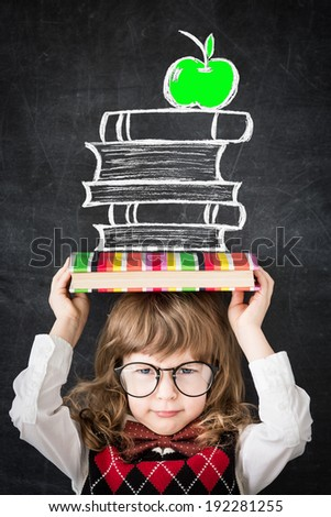 Smart kid in library. Happy child against blackboard. Education concept - stock photo