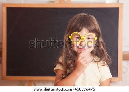 Smart kid wearing a yellow glasses stood in front of a blackboard