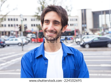 Smart latin guy in a blue shirt in the city - stock photo