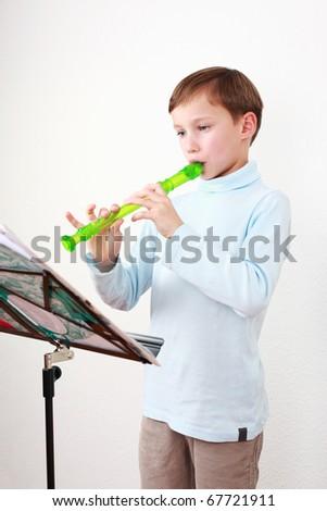 Smart little boy playing flute - stock photo