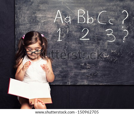 smart little girl reading a book in front of a blackboard