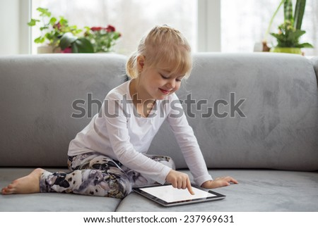 Smart little girl using tablet computer while sitting on couch in living room at home - stock photo