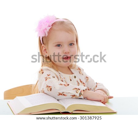 smart little girl with bow on her head sitting at a desk and reading a thick book. Girl learning grammar in a Montessori kindergarten-Isolated on white background - stock photo